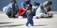 A children walks as migrants rest after disembarking from the expedition vessel Phoenix in the Sicilian harbour of Augusta, Italy June 17, 2015. REUTERS/Antonio Parrinello