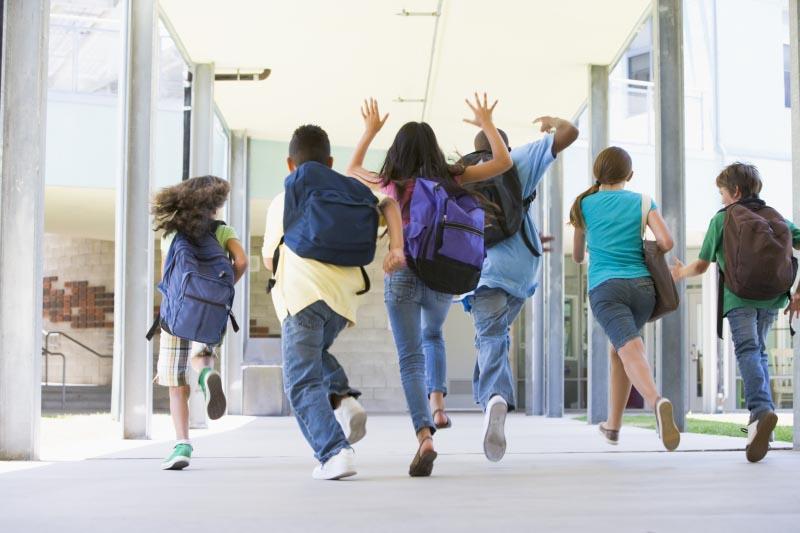 Elementary school pupils running outside